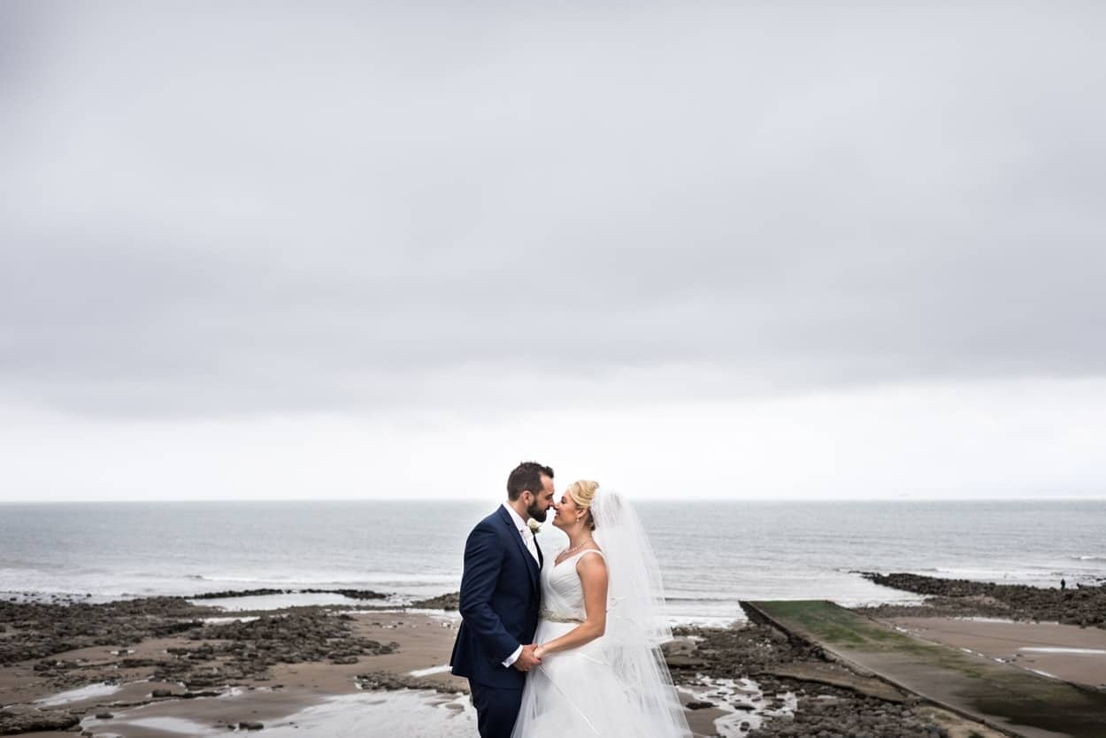 Bride and groom on beach at St Donats Castle Wedding