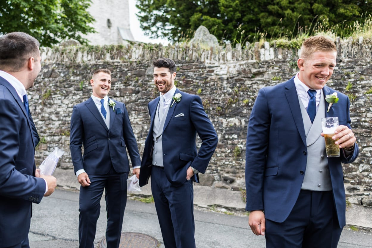 Groom laughing outside Llangynwyd Church in South Wales