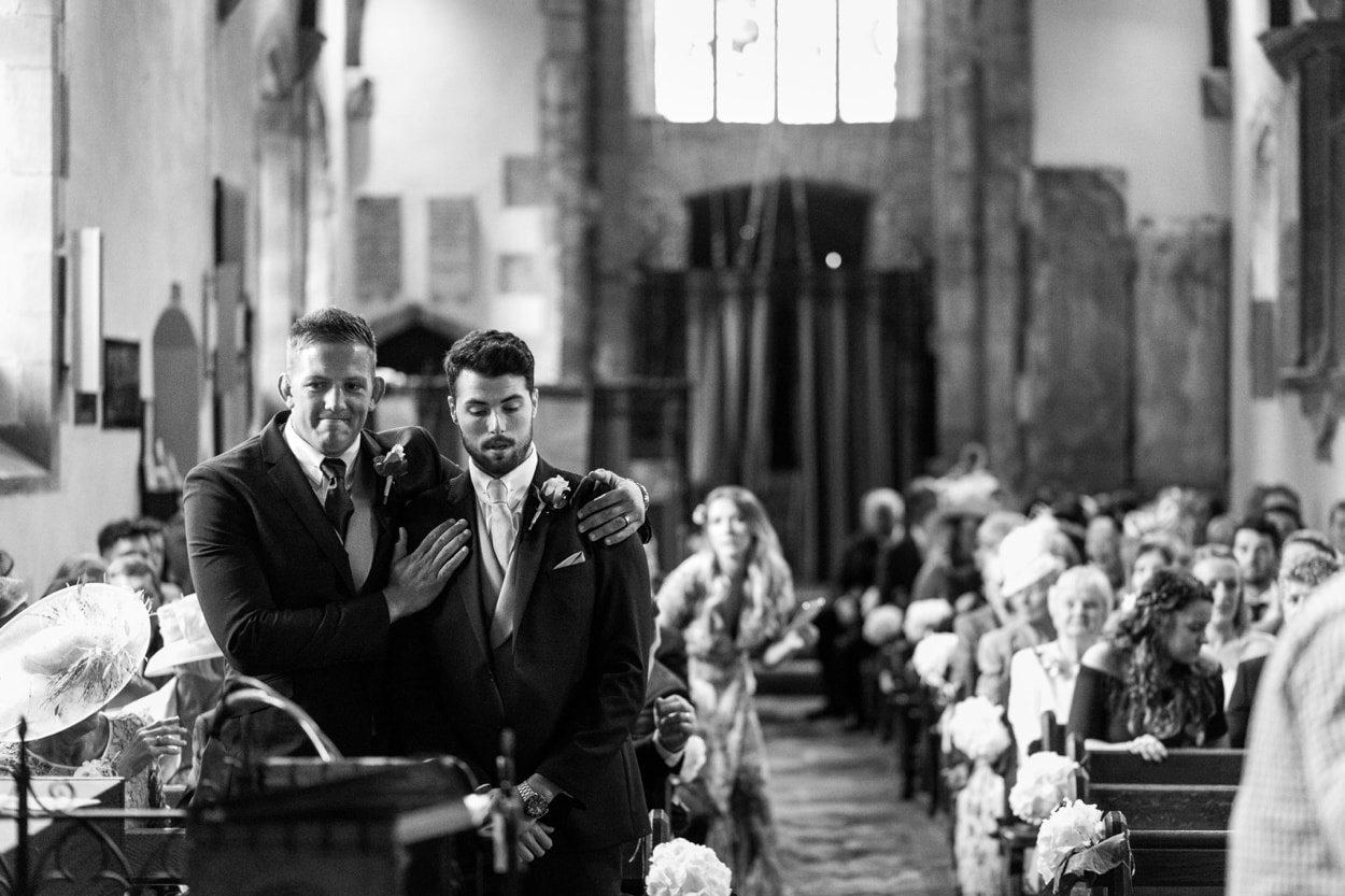 Groom waits at alter of arriving at  Llangynwyd Church in South Wales