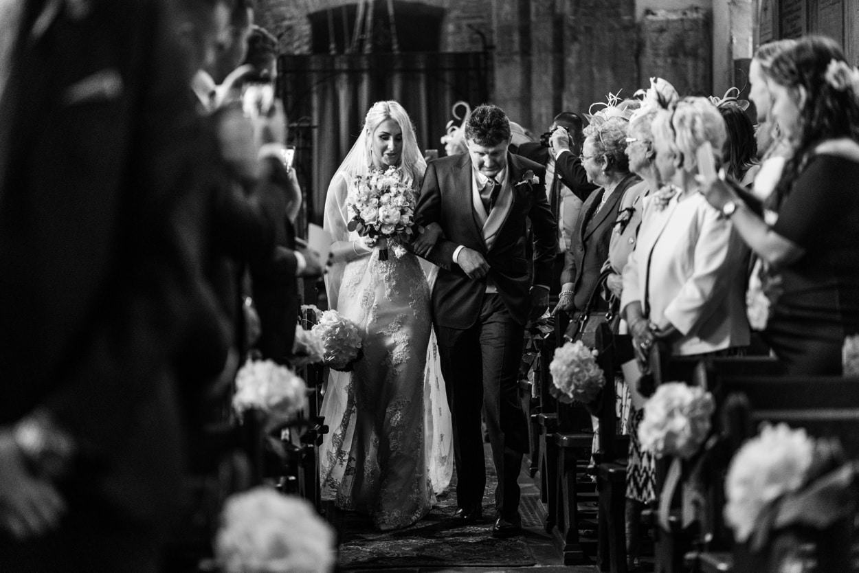 Bride and father walks down aisle arriving at  Llangynwyd Church in South Wales