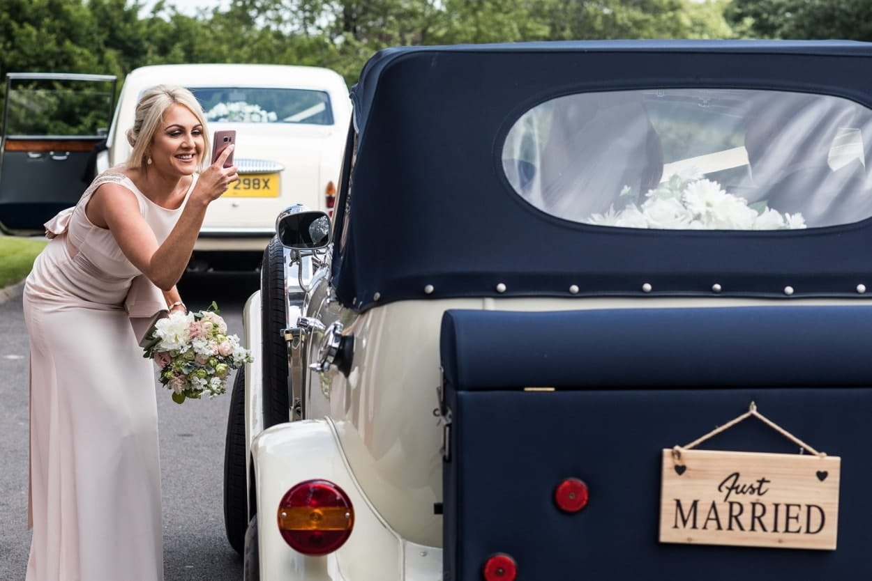 Bridesmaid take picture of bride and groom in car