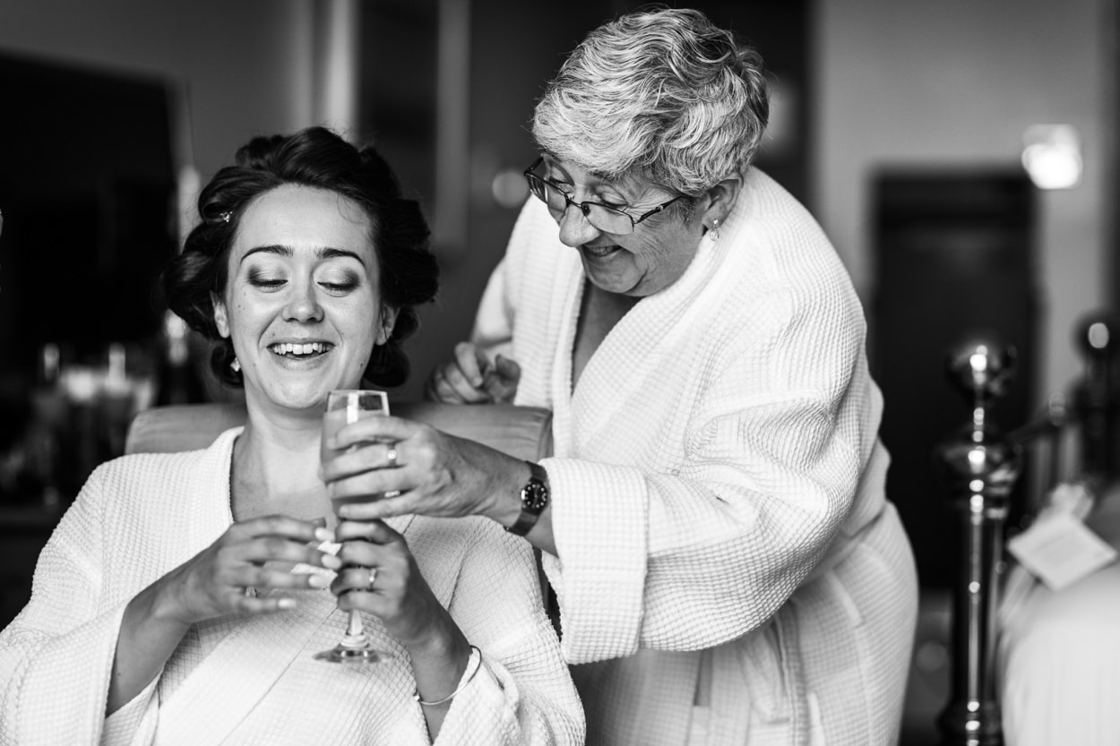Bride's mum hands her a glass of champagne