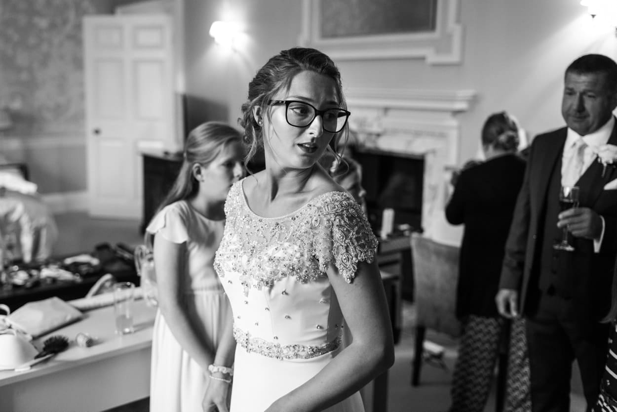 Bride in glasses getting dressed at a Nanteos wedding
