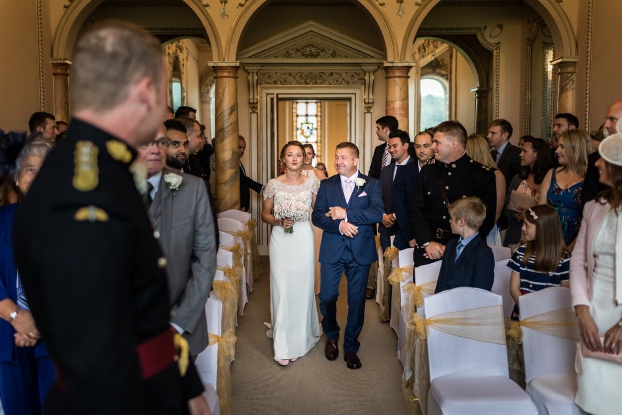 Bride walks down aisle with father at Music Room at Nanteos