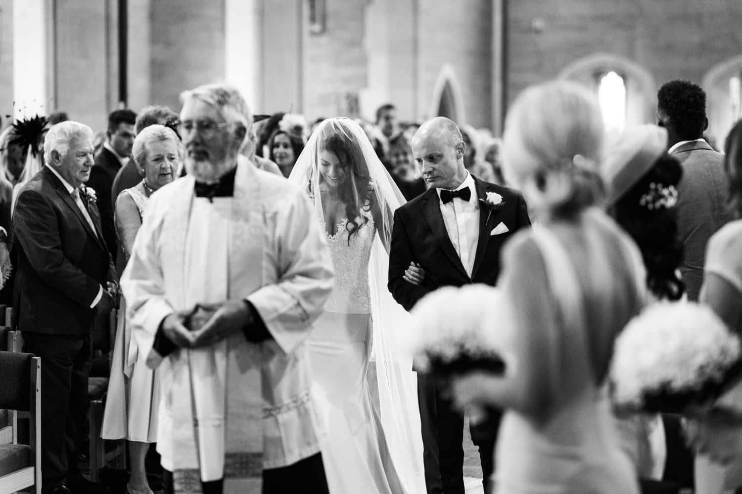Bride walks up aisle at All Saints Church , Porthcawl