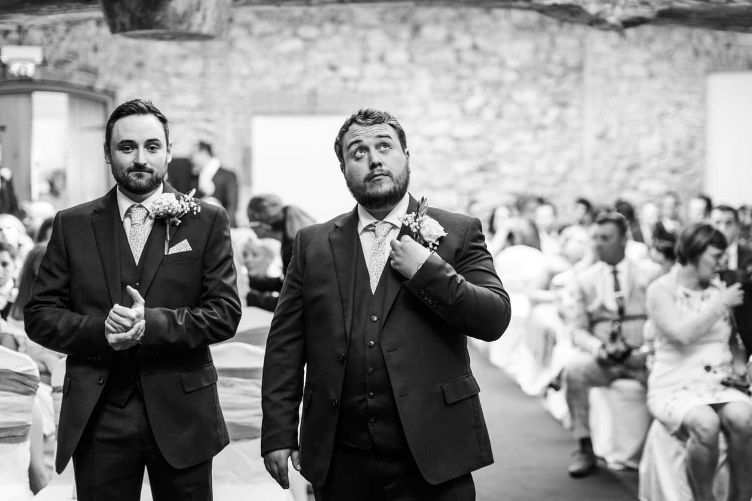 Groom looks up nervously whilst waiting for bride