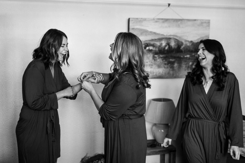 Bridesmaids laughing during preps at summer wedding at Pencoed House