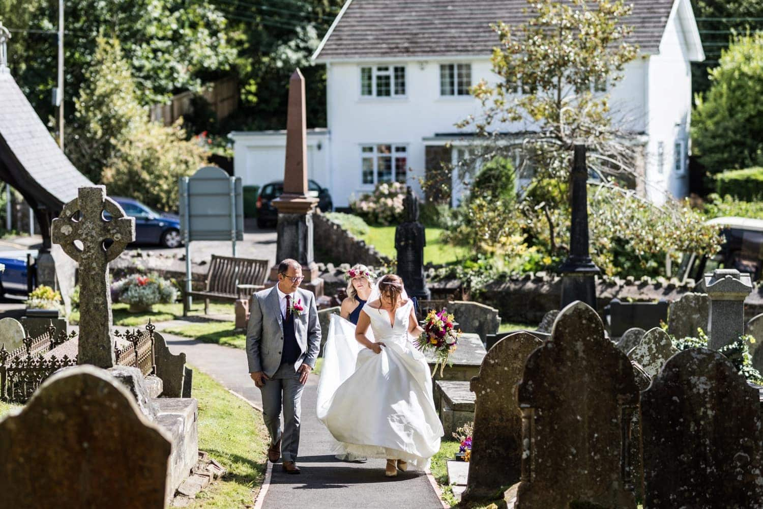 Bride walks up path at wedding in St Catwgs Church in Pentyrch, South Wales