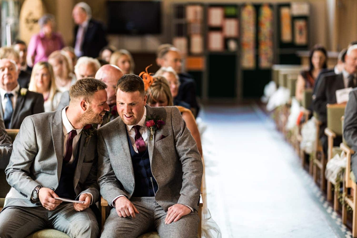 Best man talks to groom at at wedding in St Catwgs Church in Pentyrch, South Wales