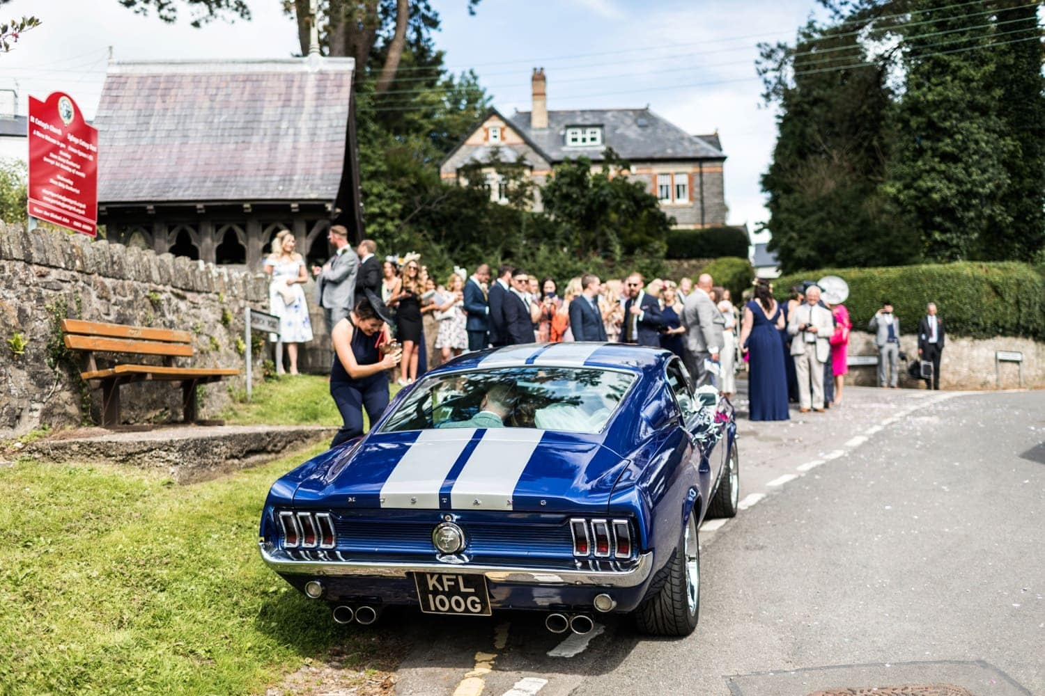 Bride and groom drive away in Ford Mustang at a South Wales wedding