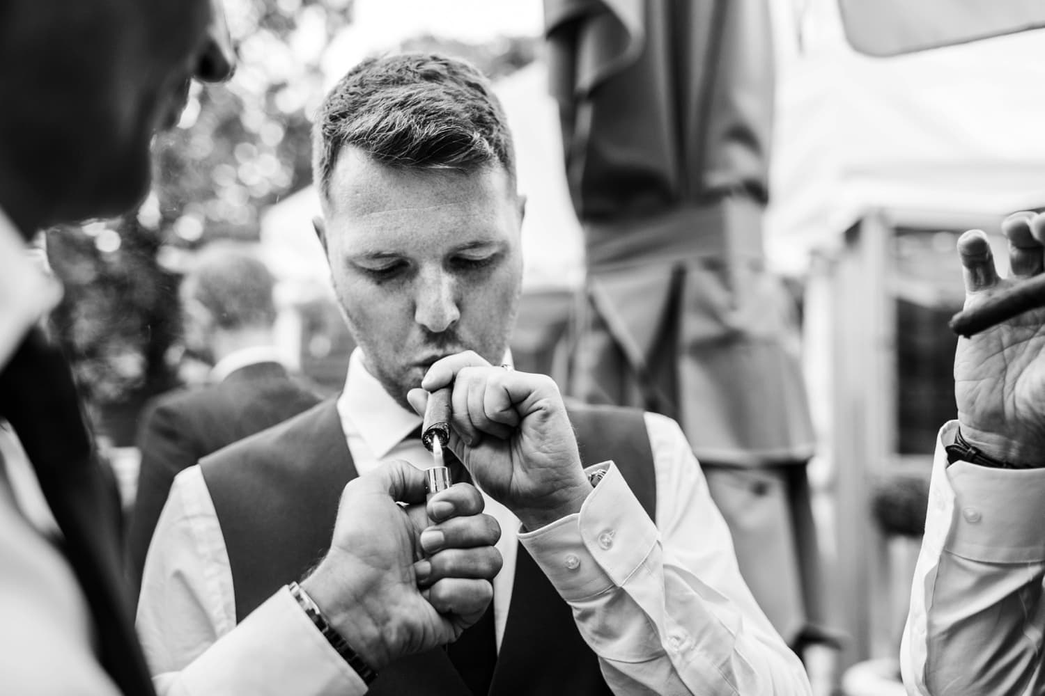 Groom lighting cigar at summer wedding reception at Pencoed House in South Wales