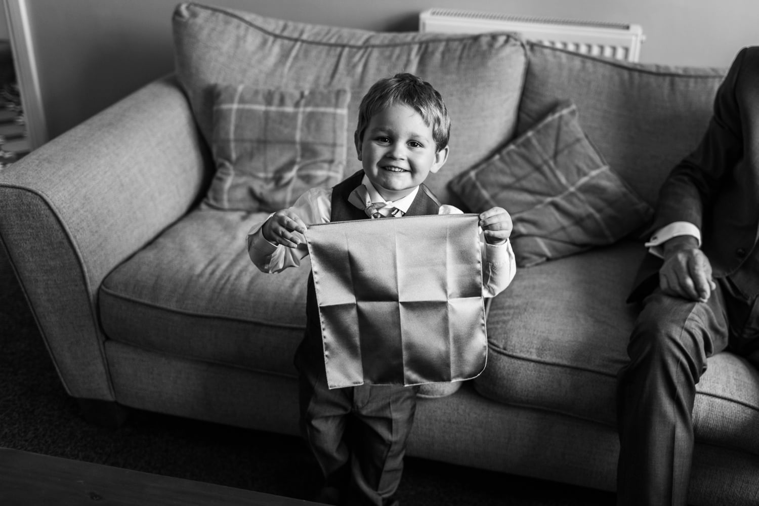Page boy holds handkerchief