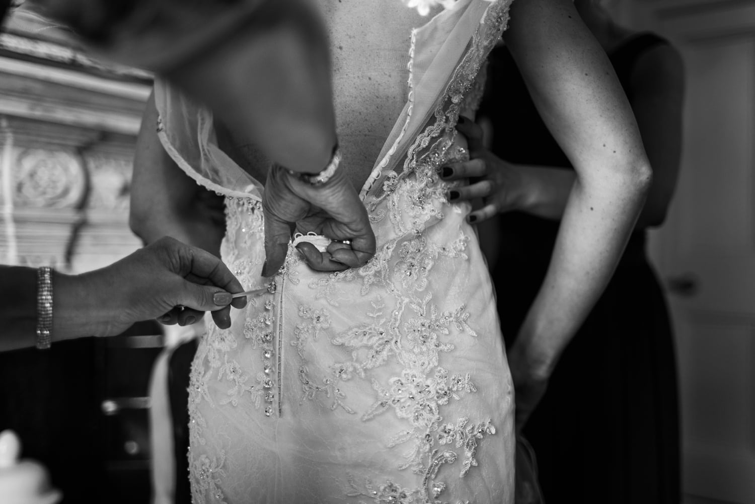 Wedding dress being buttoned at Clevedon Hall in Somerset