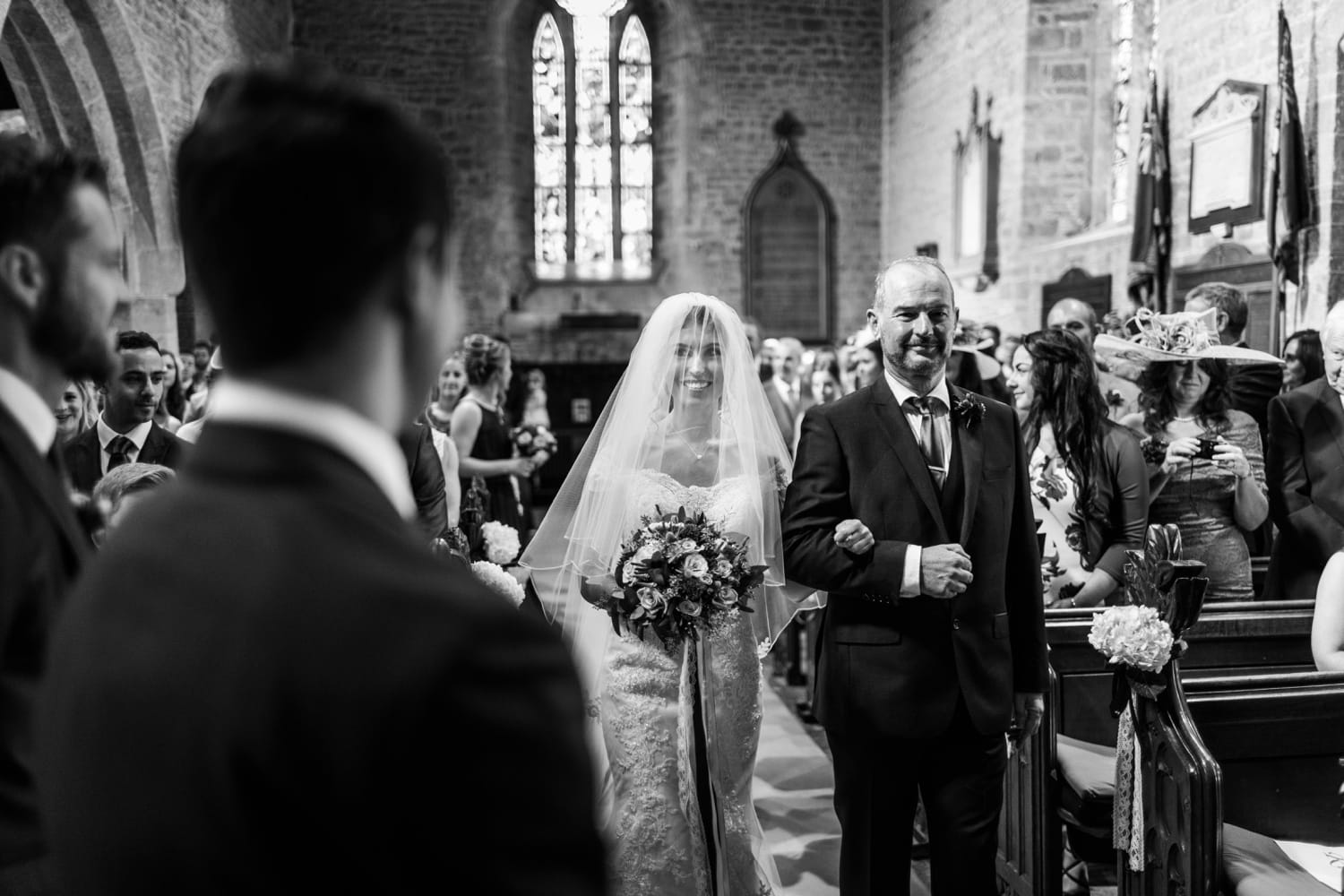Bride and father walking down the aisle at St Andrews Church in Clevedon, Somerset