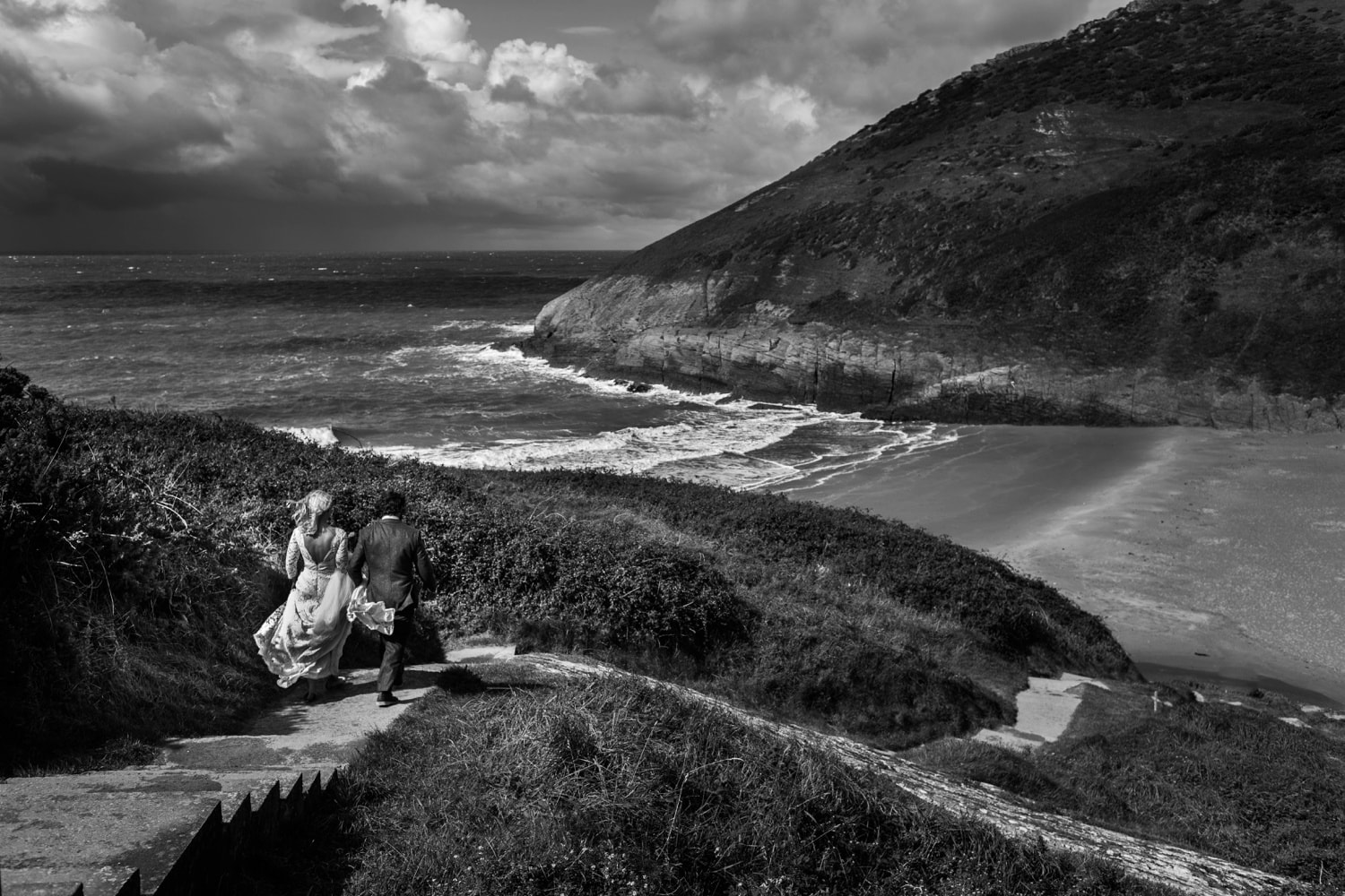 Bride and groom walking to Mwnt Beach in Ceredigion, Wales
