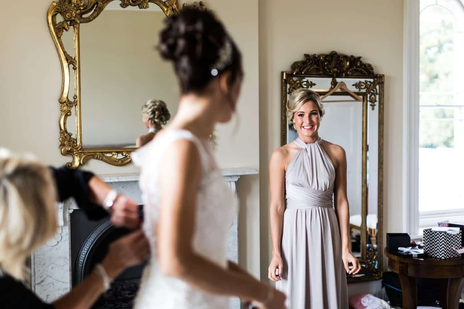 Bride's sister watching her putting on dress