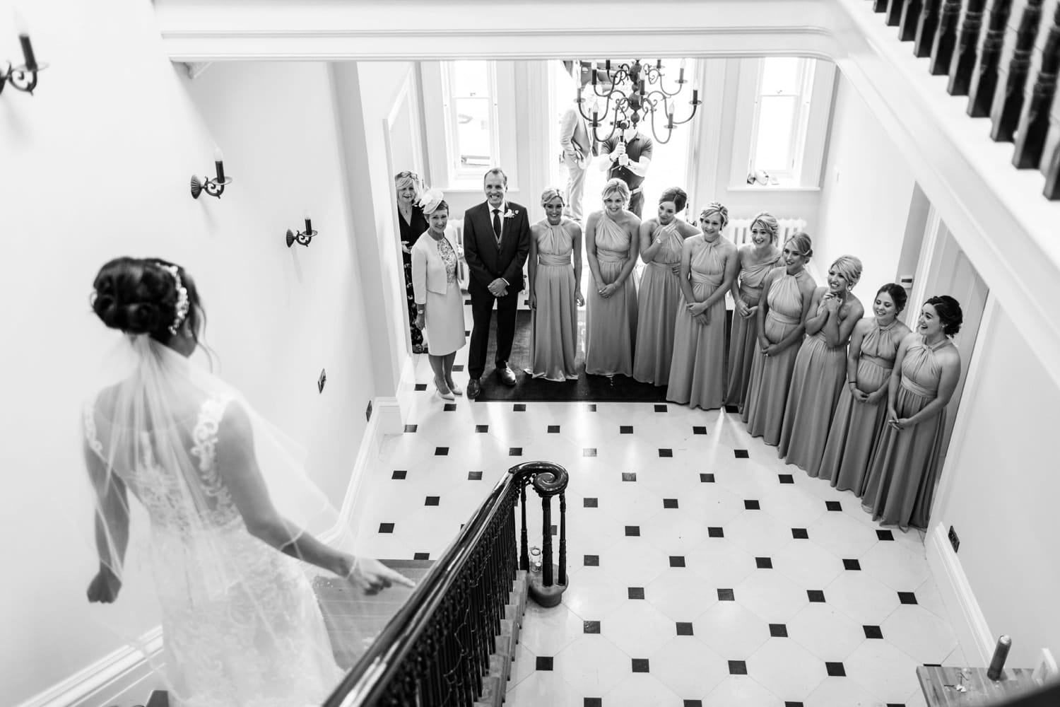 Bridesmaid watch as brides descends down stairs at St Tewdrics House