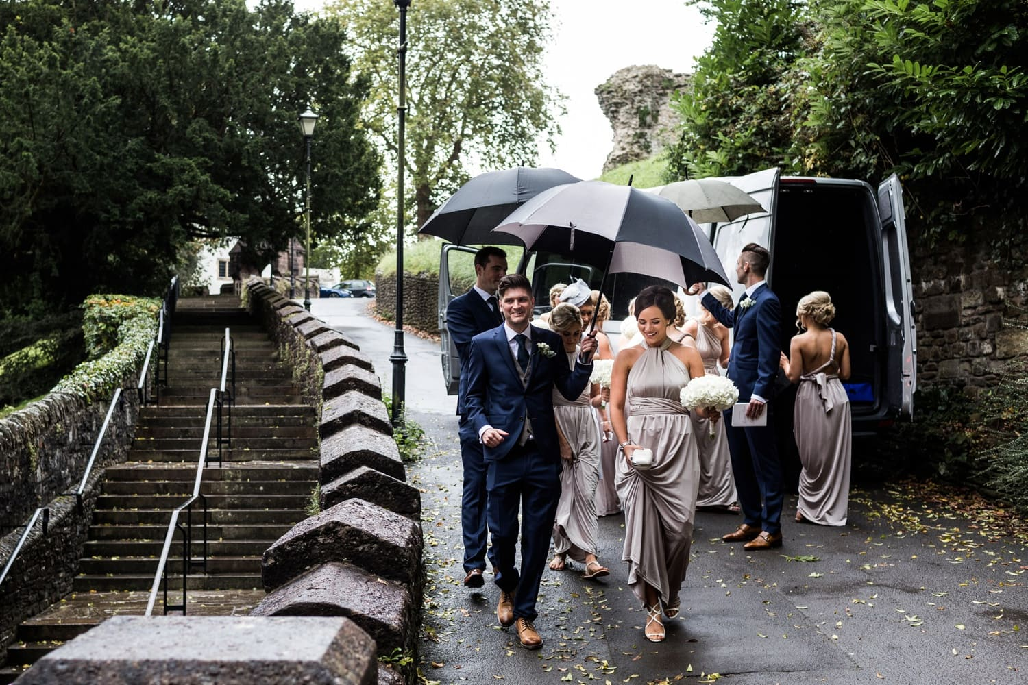 Bridesmaids escort to church under umbrellas