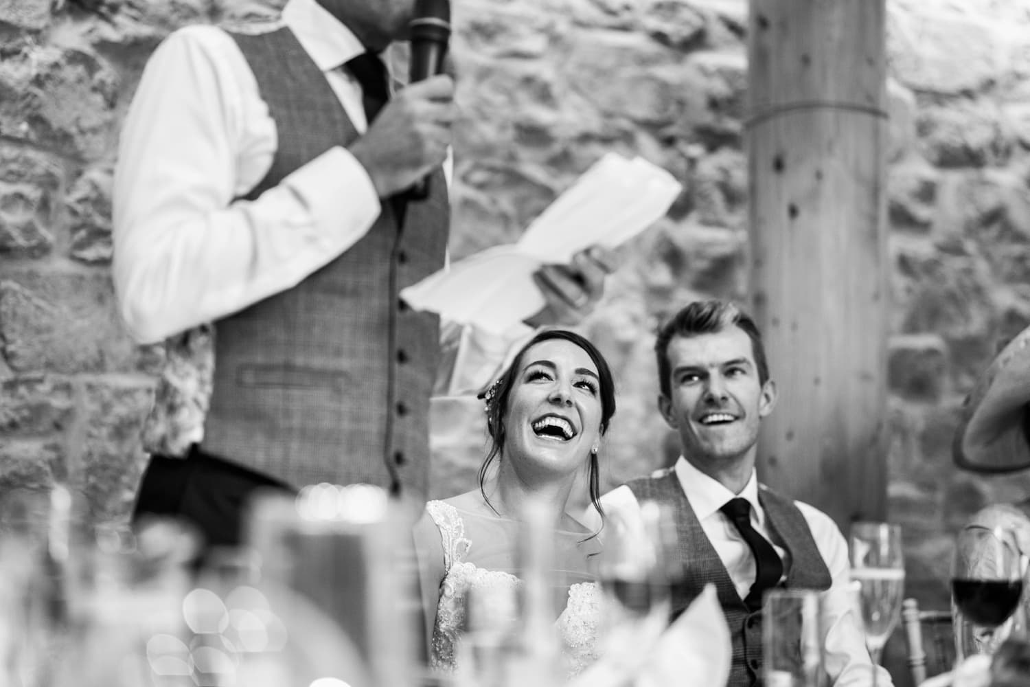 Bride looks on as father gives wedding day speech