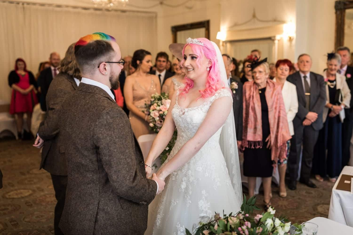 Bride with pink hair and groom with multi coloured hair getting married at Peterstone Court