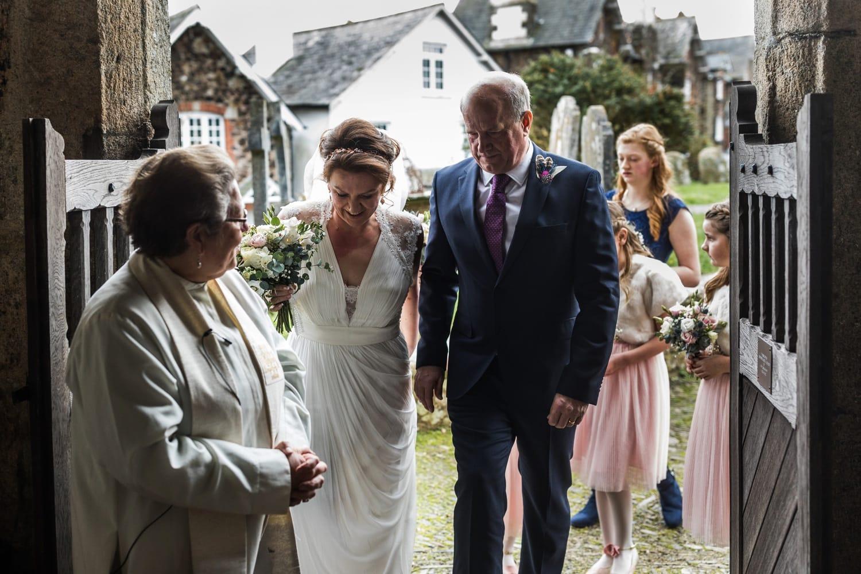 Bride and father walk through church door