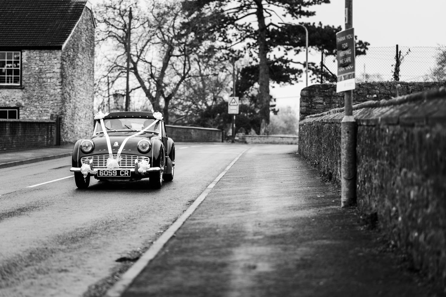 Bride arriving in classic sports car at church for Monmouthshire wedding