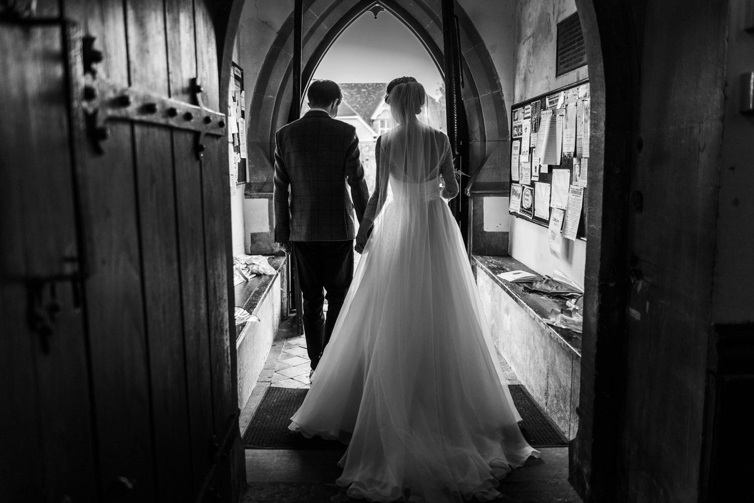 Bride and groom walk through church door