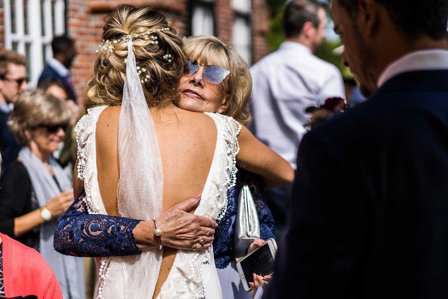 Mother of the groom hugs bride
