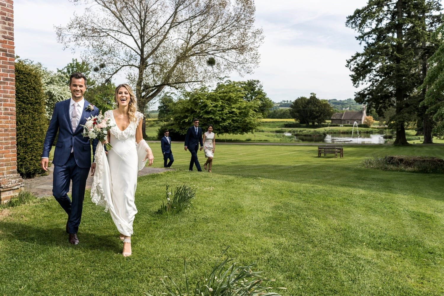 Bride and groom laugh as walking at Llansantffraed Court