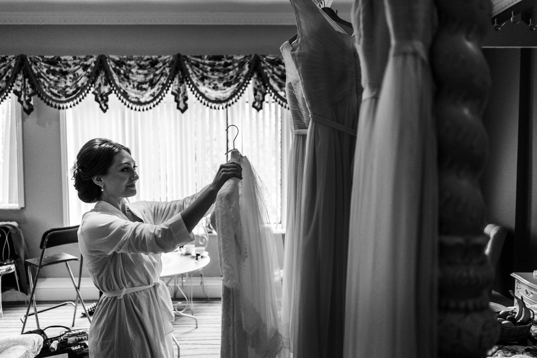 bride hanging up dress for summer wedding at miskin manor