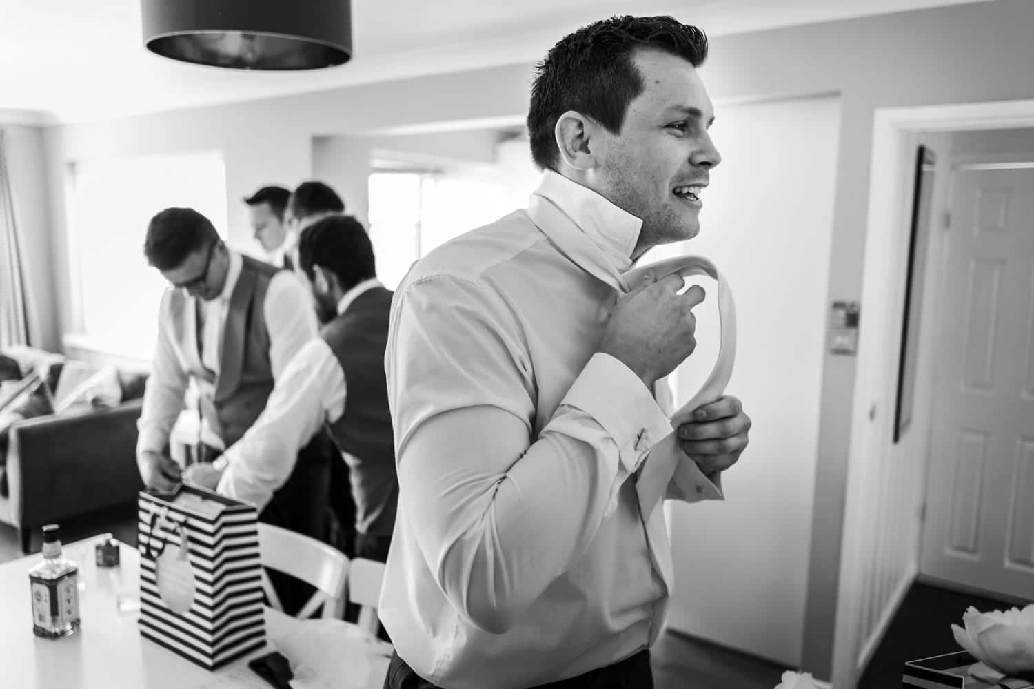 Groom puts tie on for a 2010 Clubhouse Wedding