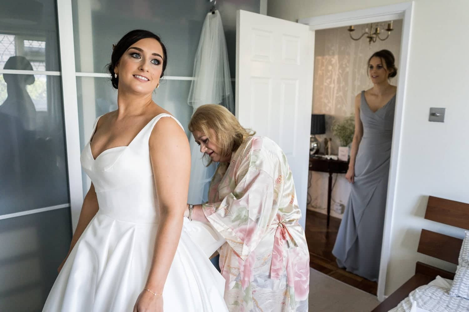 Bride puts dress on for a 2010 Clubhouse Wedding