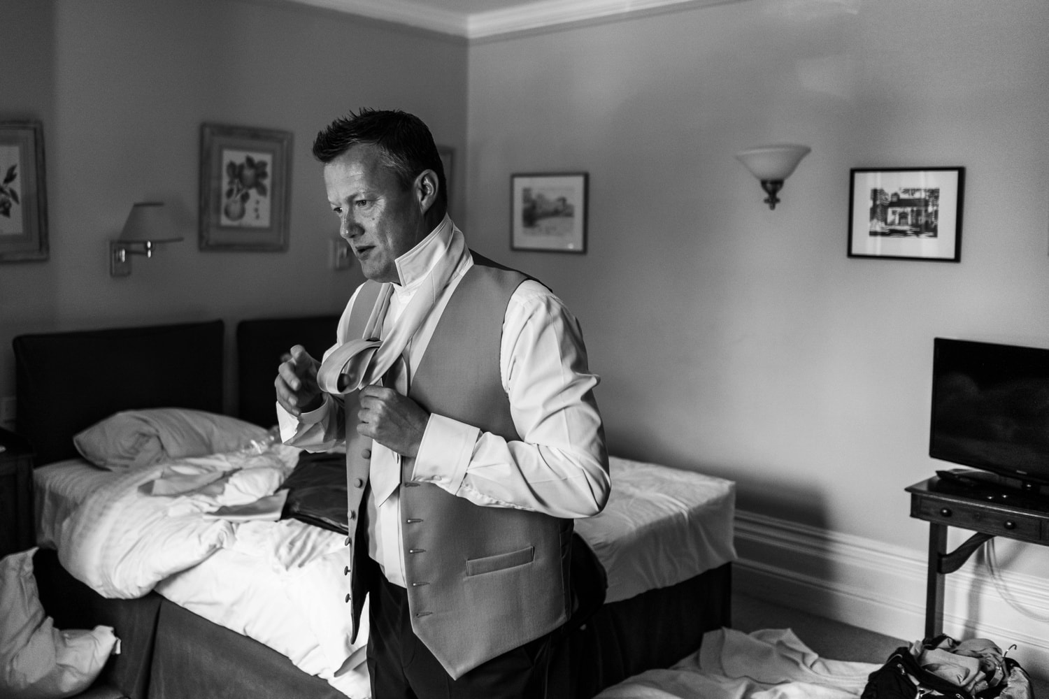 Groom puts on tie at a Glanusk Park Estate wedding