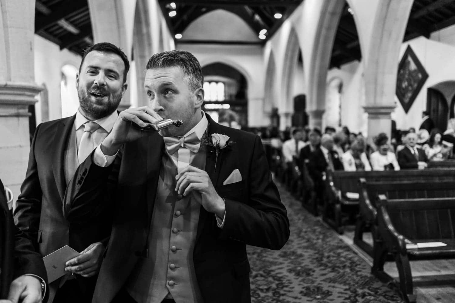 Groom swigs from hip flash at church alter