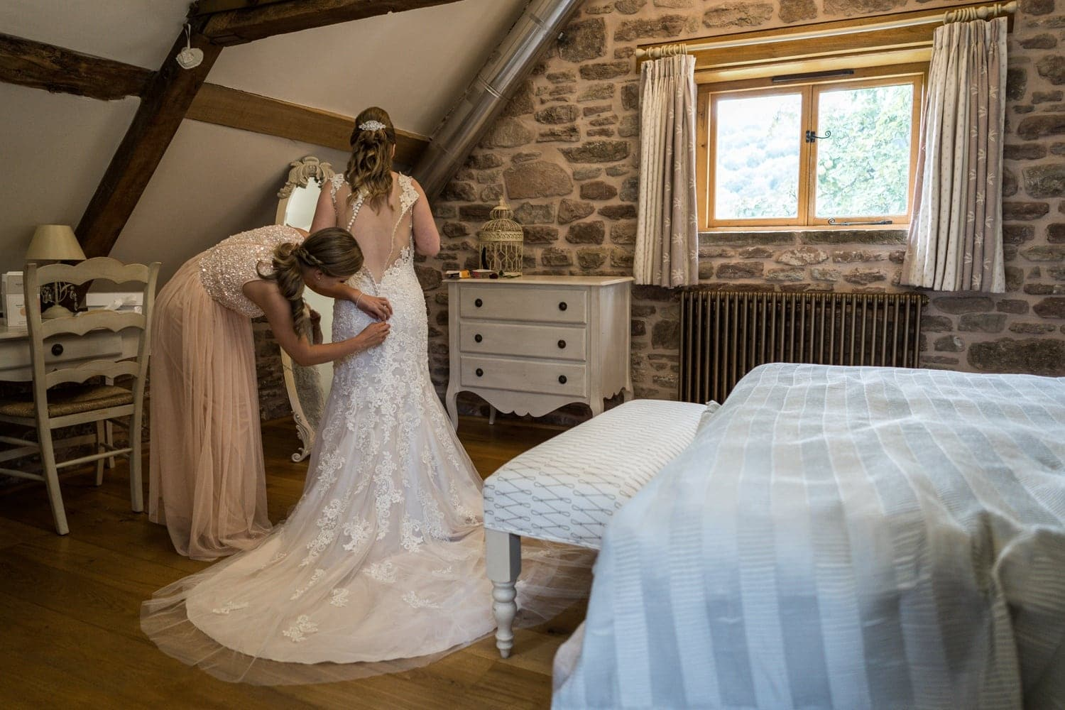 Bride puts dress on at Herefordshire wedding venue Flanesford Priory