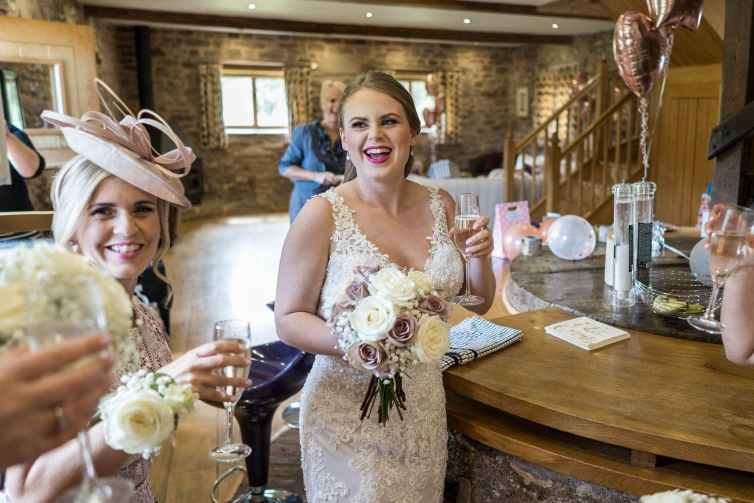 Bride has champagne at Herefordshire wedding venue Flanesford Priory