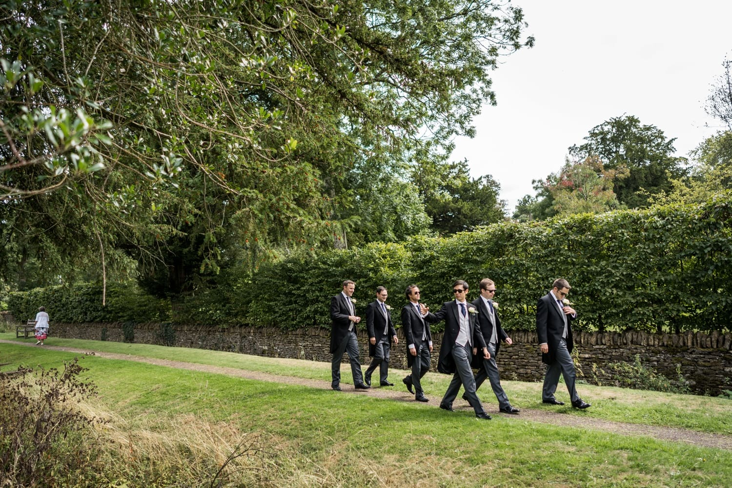 Groom and ushers walking to Great Tew church for a Cotswold wedding