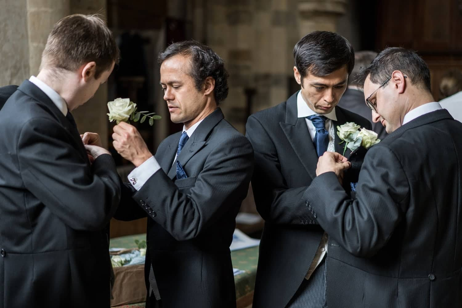 Groom and ushers put on flowers at Great Tew church for a Cotswold wedding