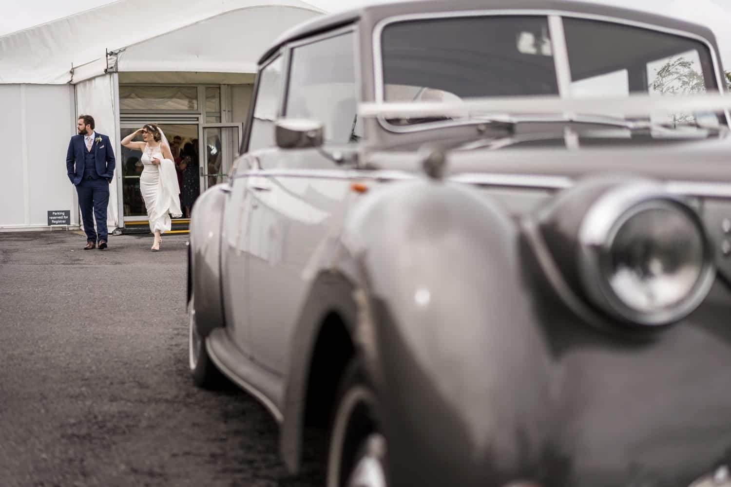 Bride and groom walk to wedding car at South Wales wedding at Ocean View