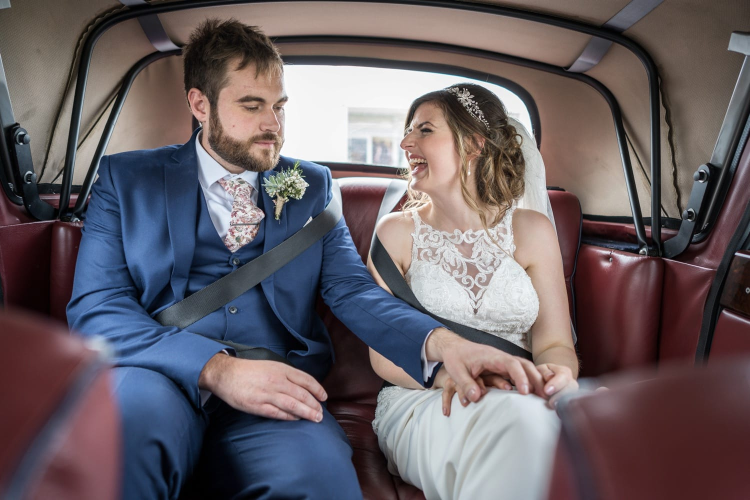 Bride and groom laugh in back of wedding car