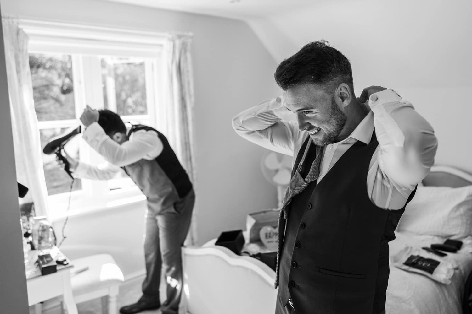 Groom does his tie at St Tewdrics House, Monmouthshire, South Wales