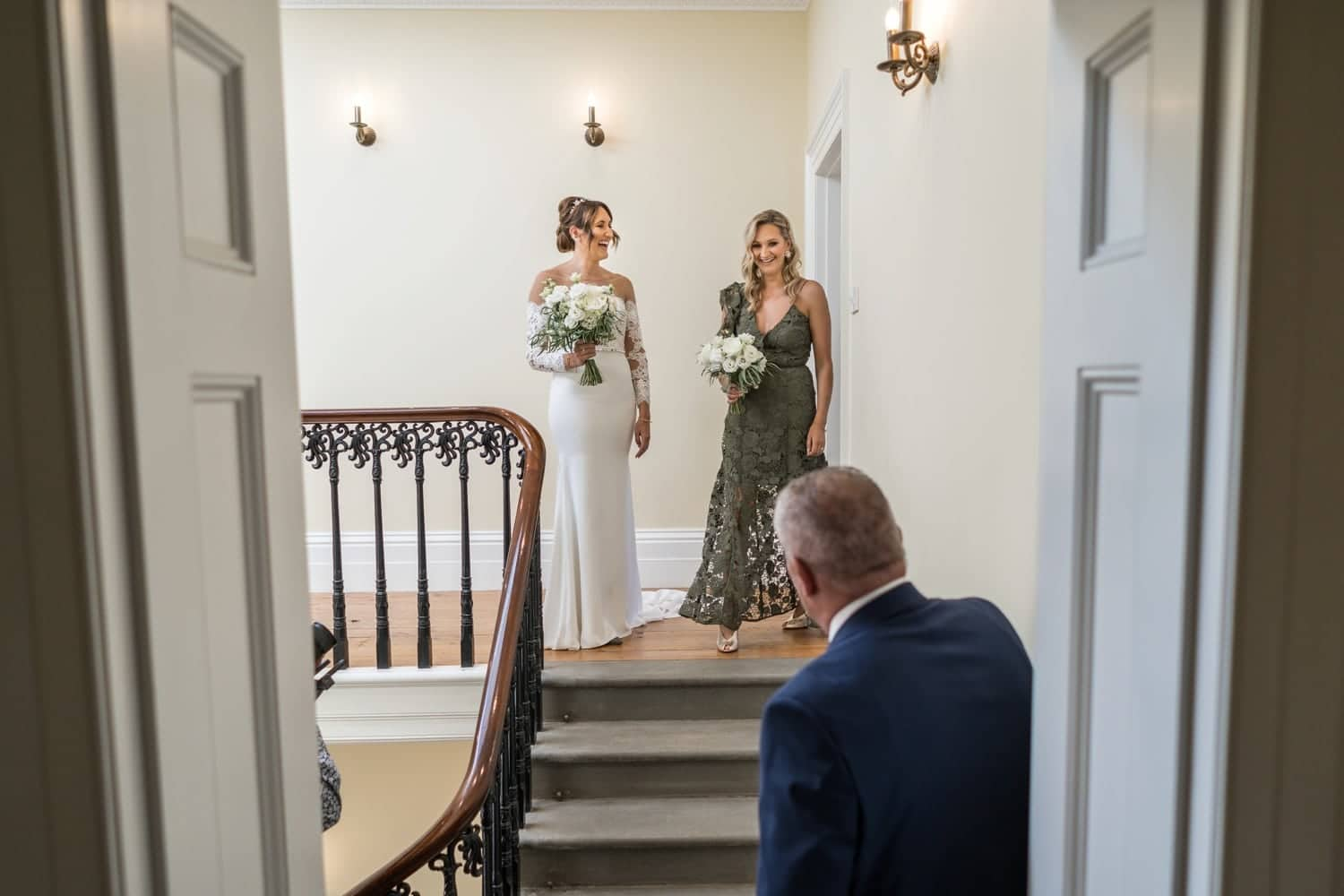 Bride and dad on stairs at St Tewdrics House, Monmouthshire, South Wales