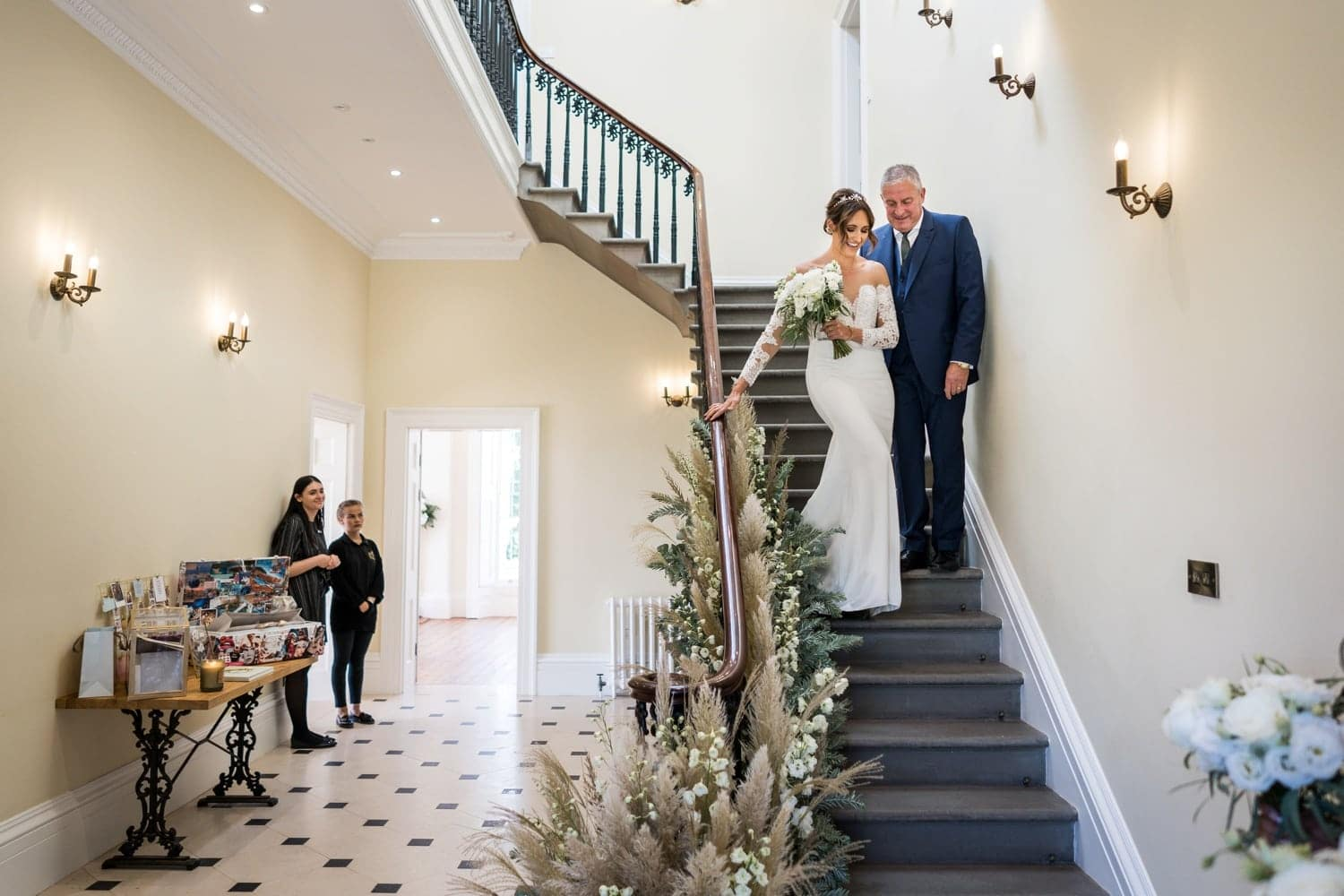 Bride and her father on stairs at St Tewdrics House, Monmouthshire, South Wales