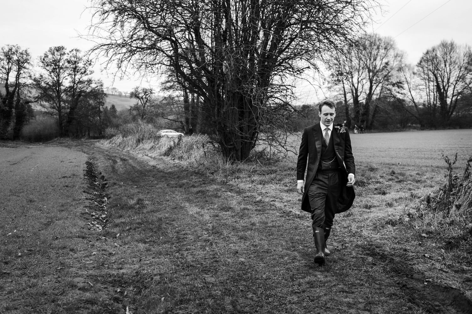 Walking through field to church wedding in Monmouthshire