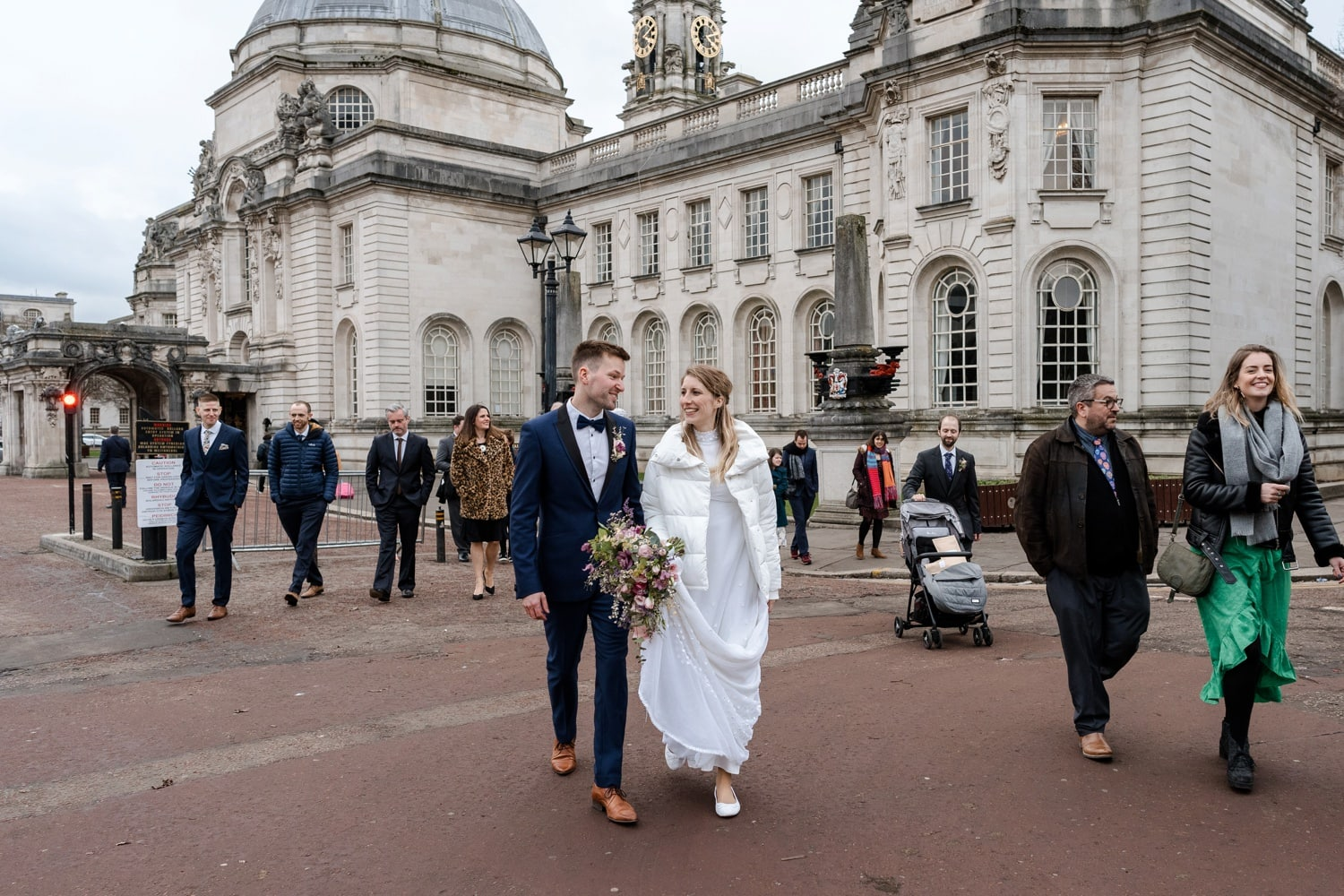 Bride and groom walking away from Cardiff City Hall