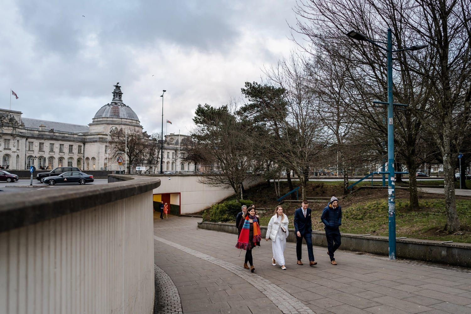 Bride walking with guest with Cardiff City Hall in background