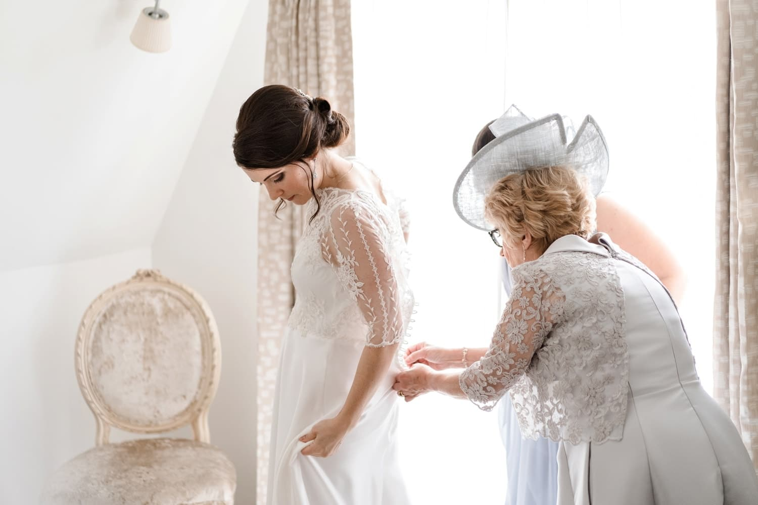 Bride's mother putting on dress