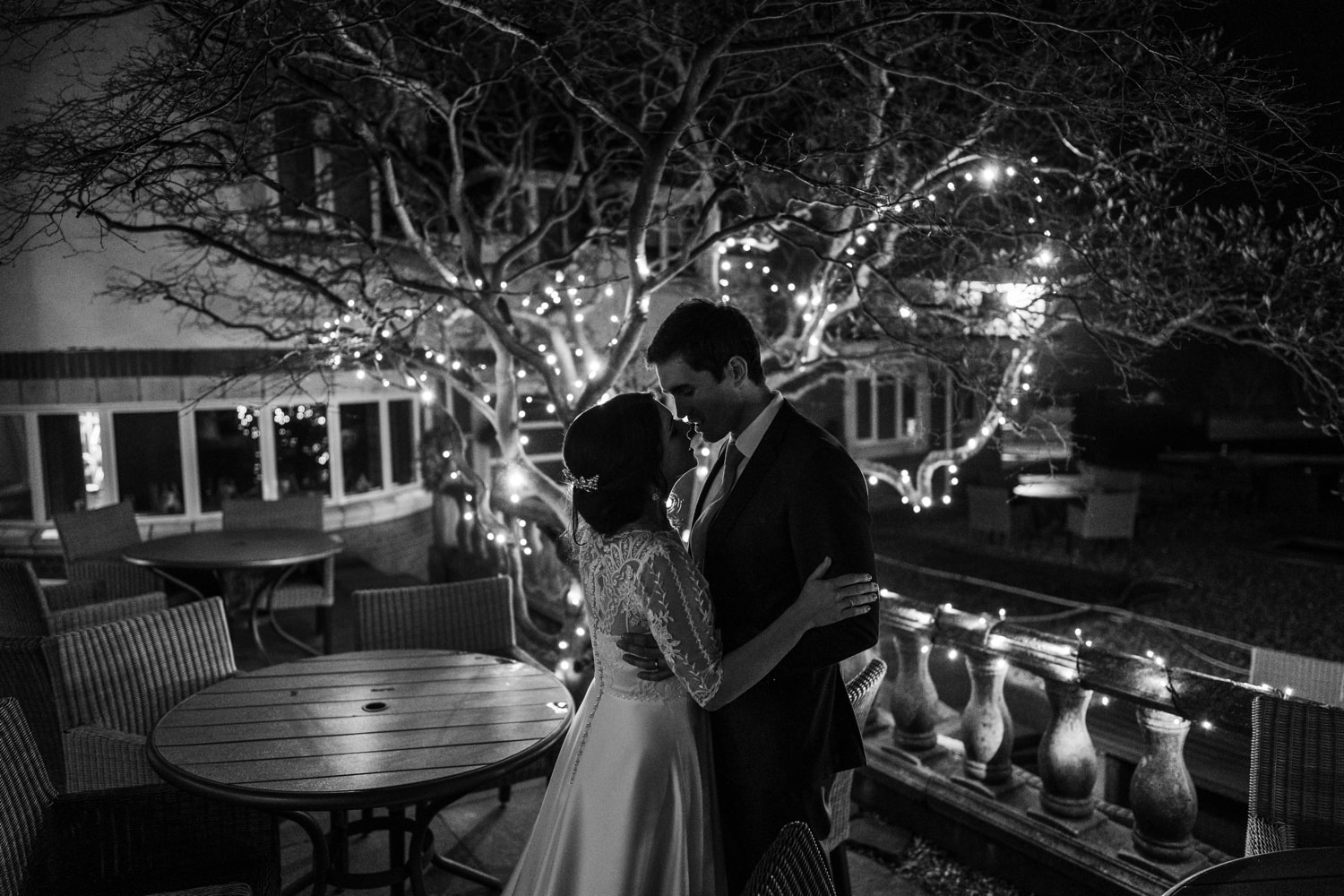 Bride and groom kissing in front of fairy lights at tHolm House in South Wales