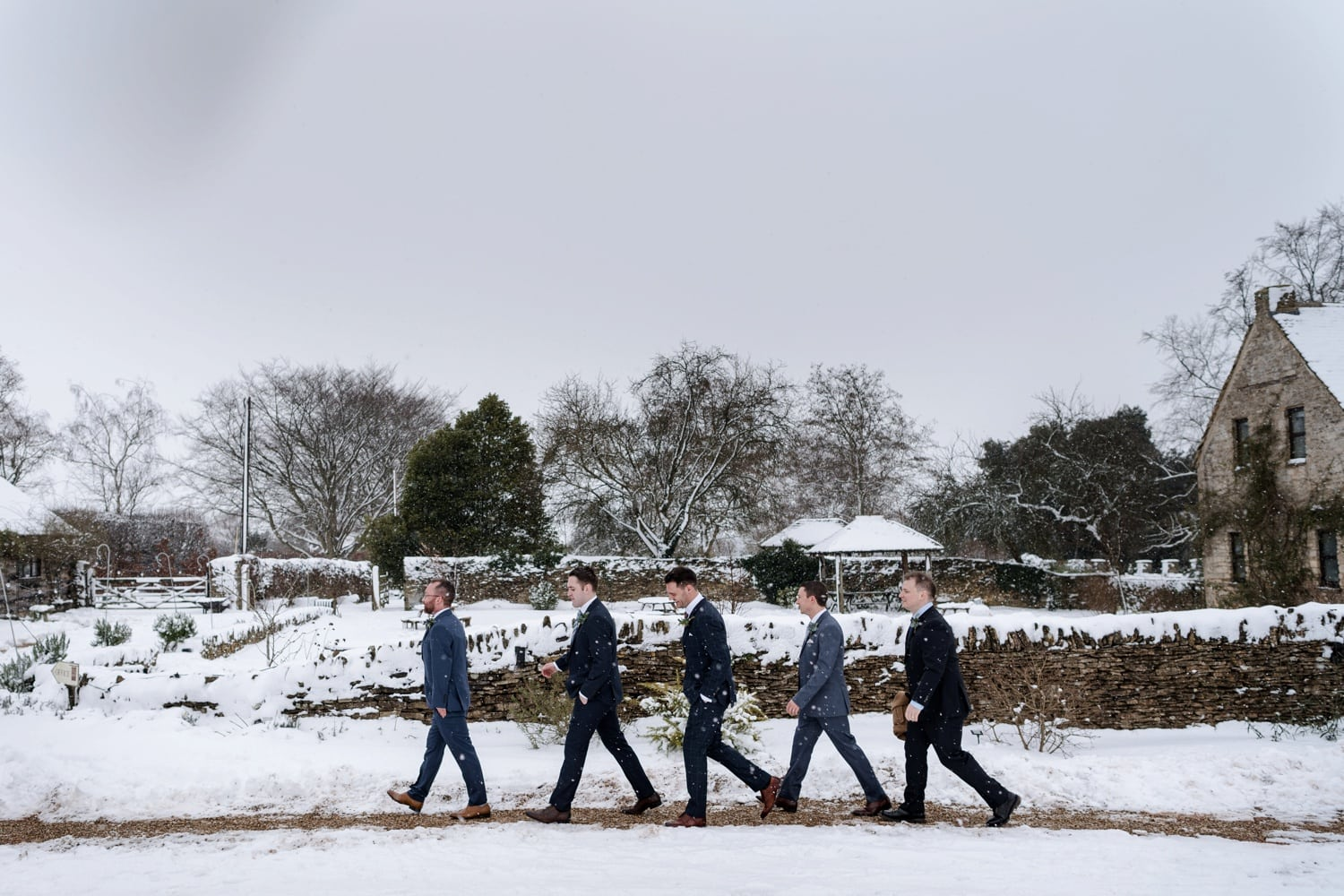 Groom and ushers walking through snow at a wedding