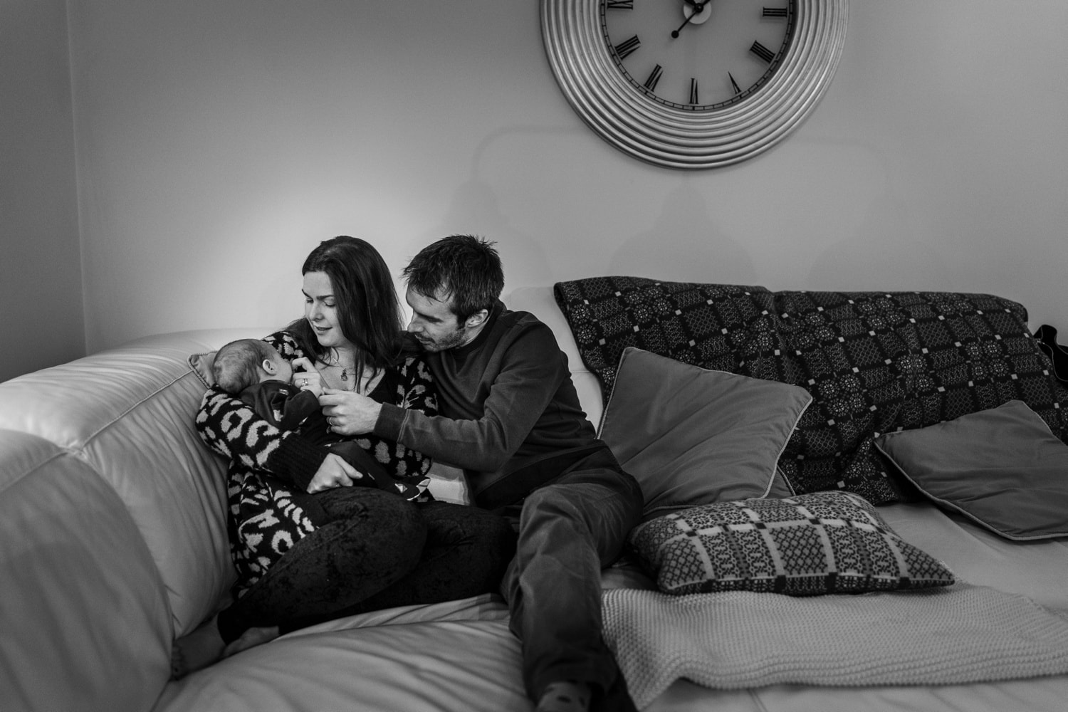 parents with new born baby all sitting on sofa
